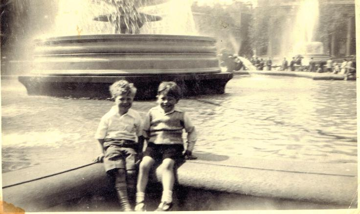 Two children sitting on the edge of the fountain at Trafalgar Square