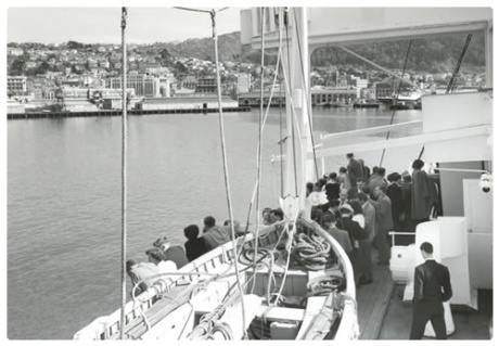 Ten Pound Poms entering Wellington Harbour in the 1950's. Peple crowded in the bow of the boat as it arrive.