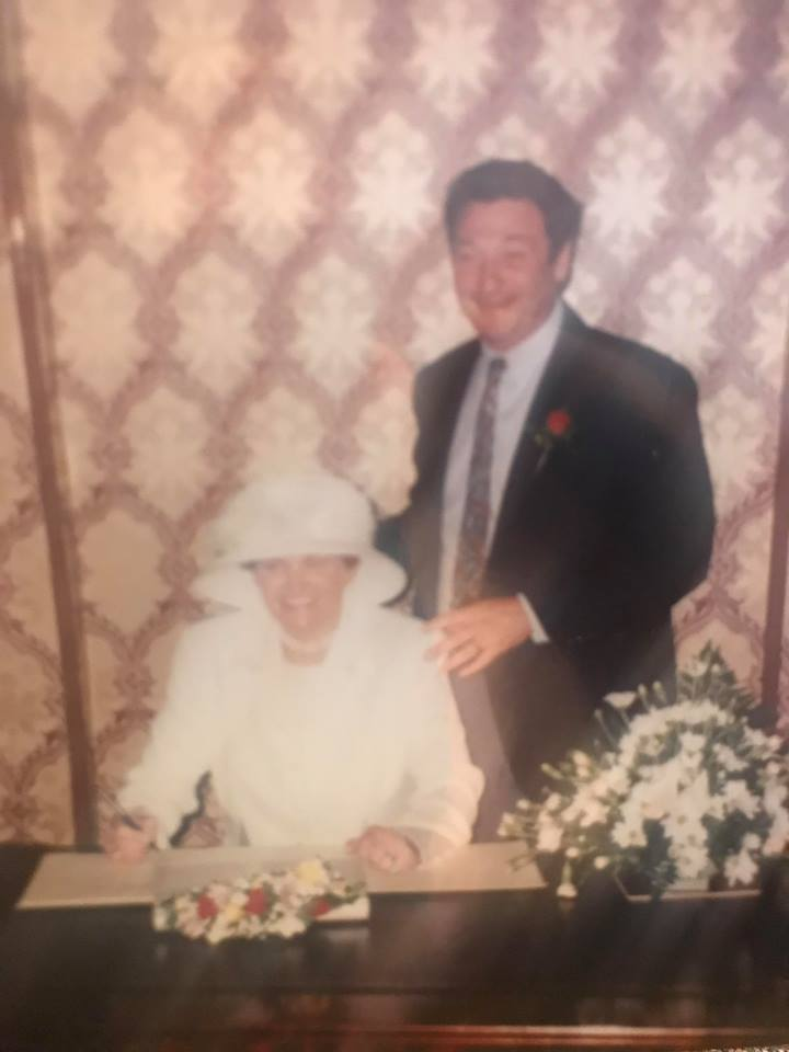 Image of woman at a wedding signing the register with man standing behind her.