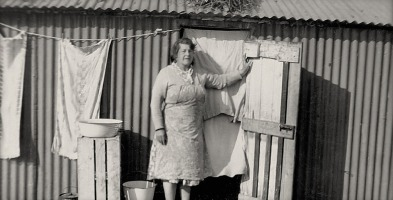 Photograph of a middle aged women outside a Hopper Hut in the hop fields of Kent. The hut is of corrugated iron. The woman is standing beside a washing line attached to the hut.
