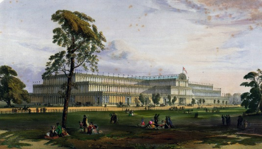 An image of the Crystal Palace showing the front image with people lying on the grass and under trees in the foreground.