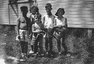 A Child of a Ten Pound Pom standing with a group of four other children.
