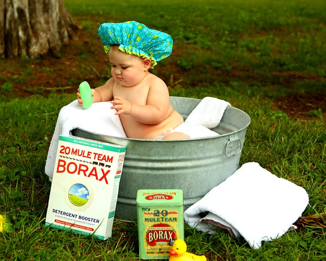A photograph of a small child in an old tin bath. Child holding soap.