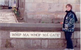 Travel sometimes results in unintended consequences. This image shows a female standing beside a road name in England. Whipmawhopmagate!