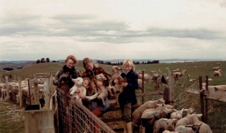Unintended consequences can result in changing lifestyles. A farming scene showing four girls holding lambs in a sheep pen reading for tailing.