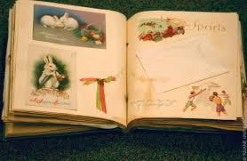 An open book showing photographs on a layout using ribbons, cards and heritage scrapbooking material.