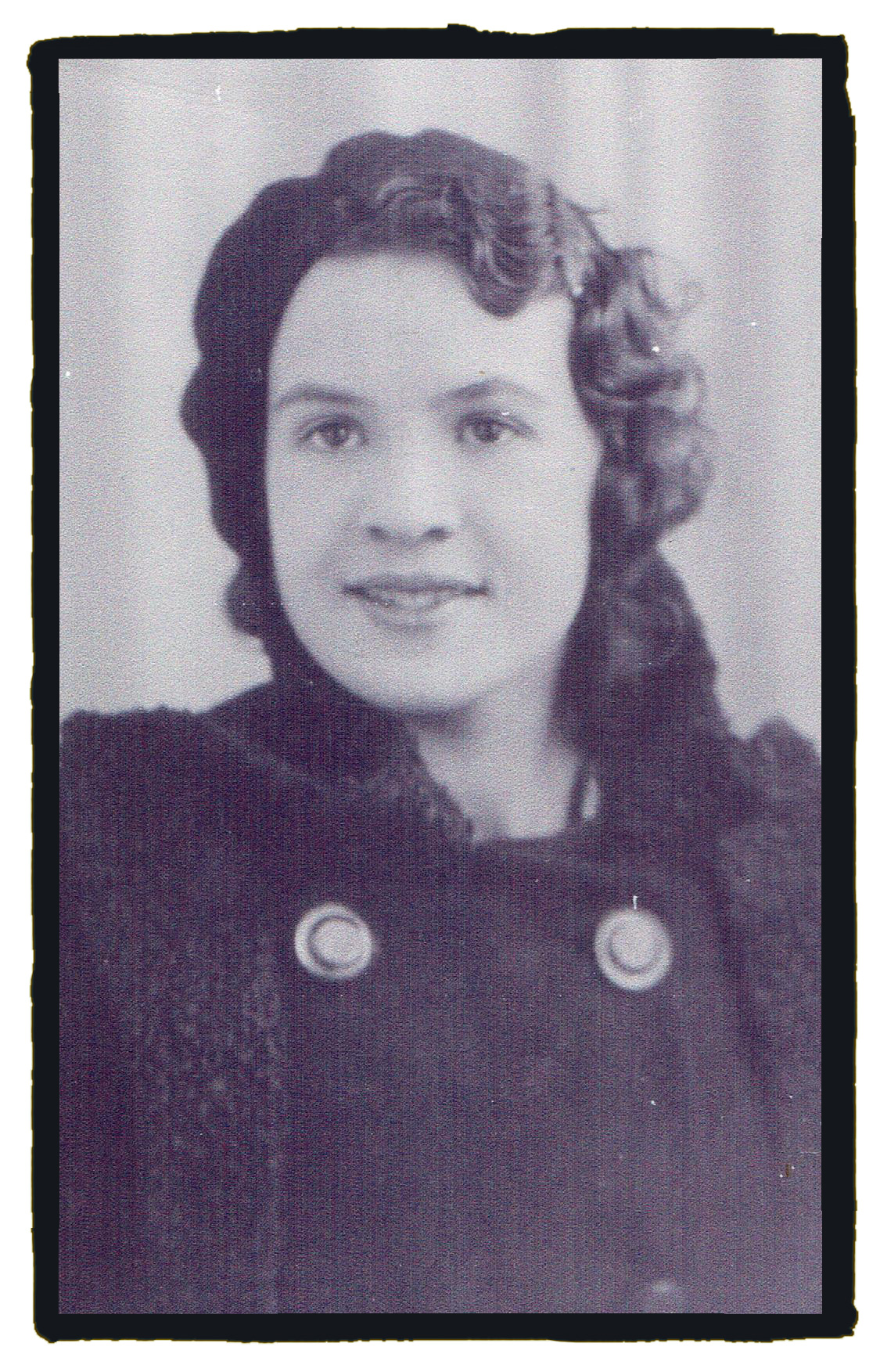 Black and white photograph of a young women taken c 1935.  She has wavy dark hair and dark brown eyes.