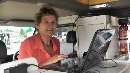 Image of a women sitting at a computer in a small campervan