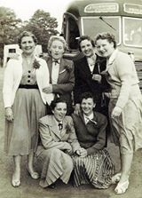 Six women posing in front of a Silvertown Coach on a charabanc outing.