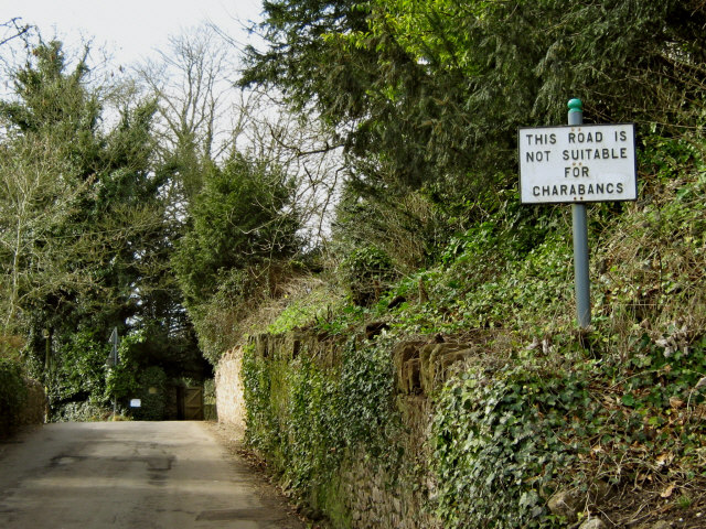 "A narrow English country road showing a road sign warning, ""Not suitable for charabancs"""