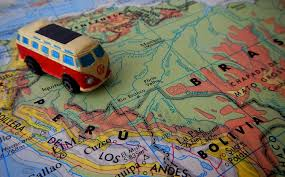 Image of a toy volkswagon sitting on a road map with a route traced on it. Titled the genealogy road trip.