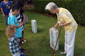Photograph of an elderly women talking to a group of young children in front of a gravestone. Depicting genealogy for children