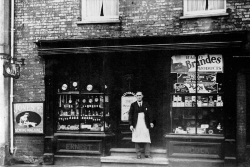 Ernest Adcock watchmaker standing outside his shop. Circa 1920